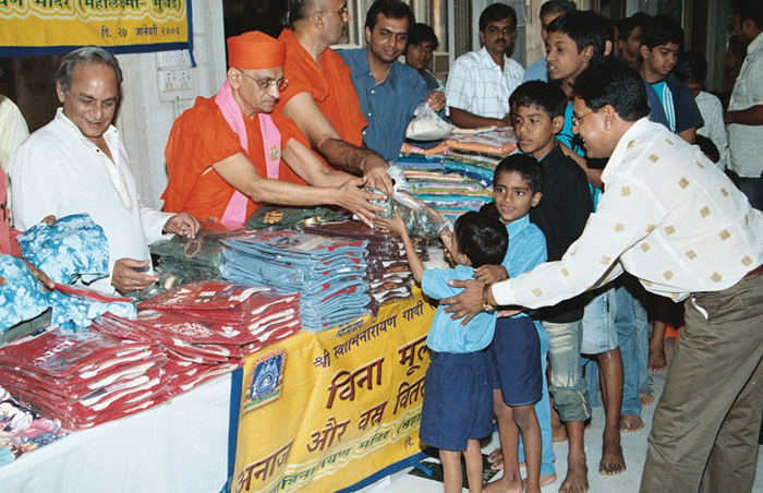 Acharya Swamishree giving aid to the needy