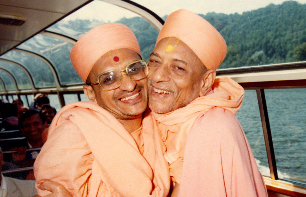 Jeevanpran Swamibapa and Acharya Swamishree Maharaj embrace on during a boat cruise at Lake District
