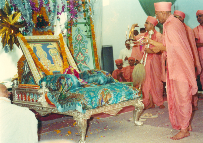 Jeevanpran Shree Muktajeevan Swamibapa performing the first aarti to Lord Shree Swaminarayan and Jeevanpran Bapashree enthroned on Shree Swaminarayan Gadi