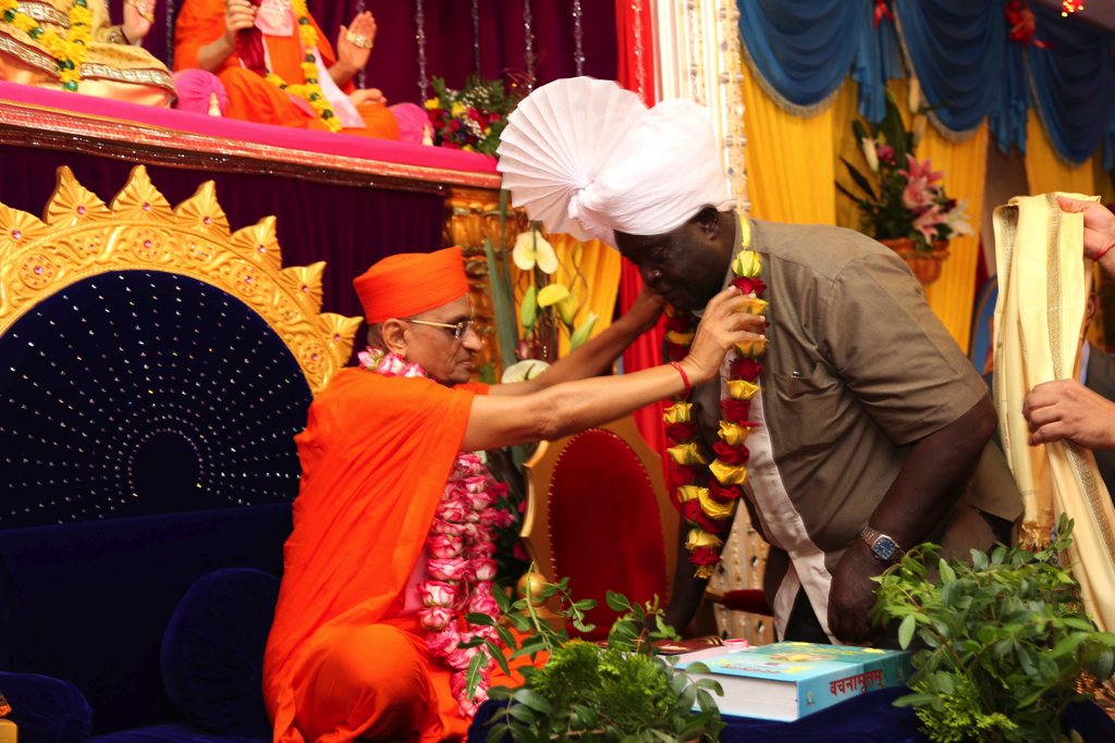 Acharya Swamishree garlands Hon. Dr. Noah Wekesa (Minister for Forestry and Wildlife