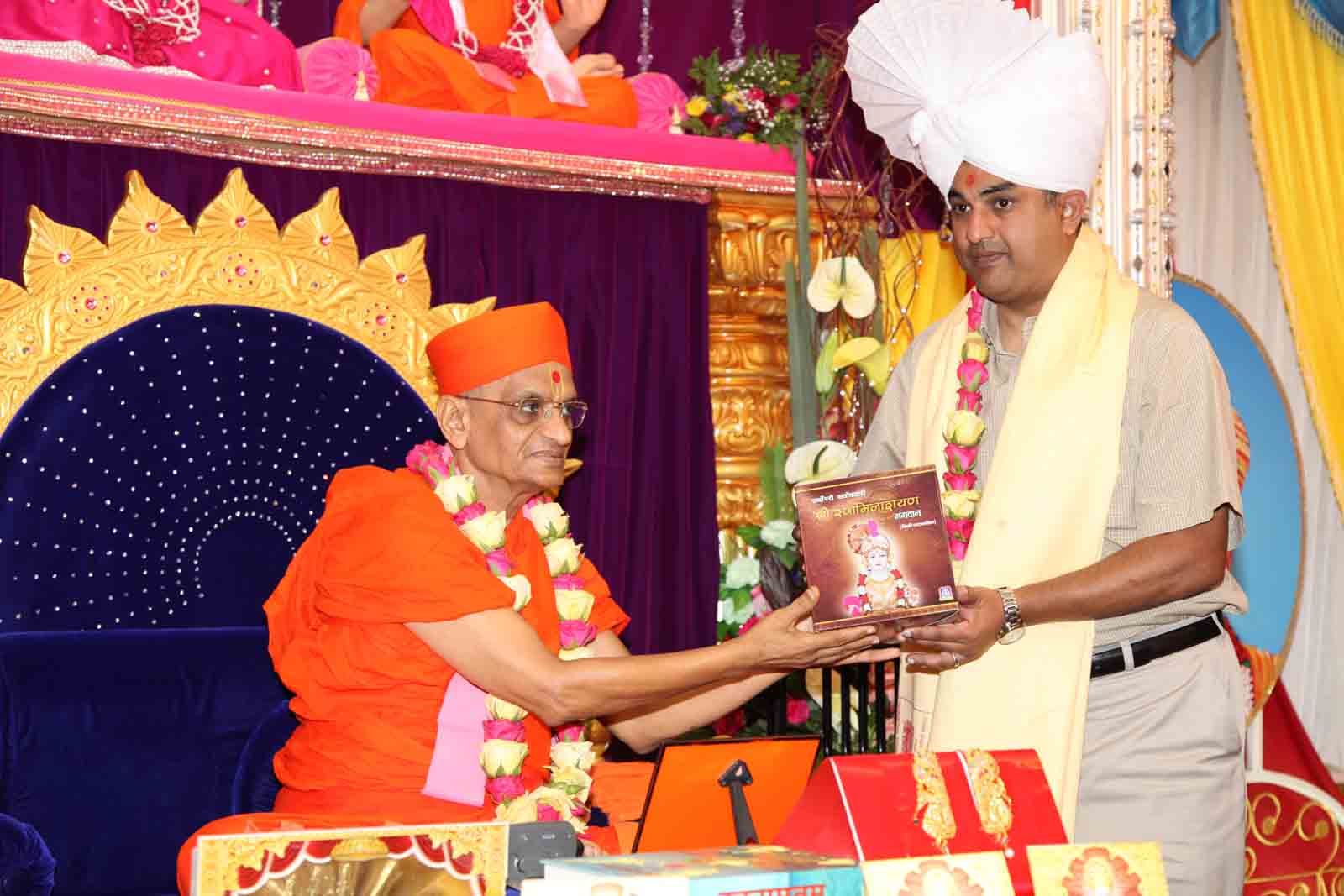 The guest receives a set of the Sarvopari Swaminarayan serial CD's from Acharya Swamishree