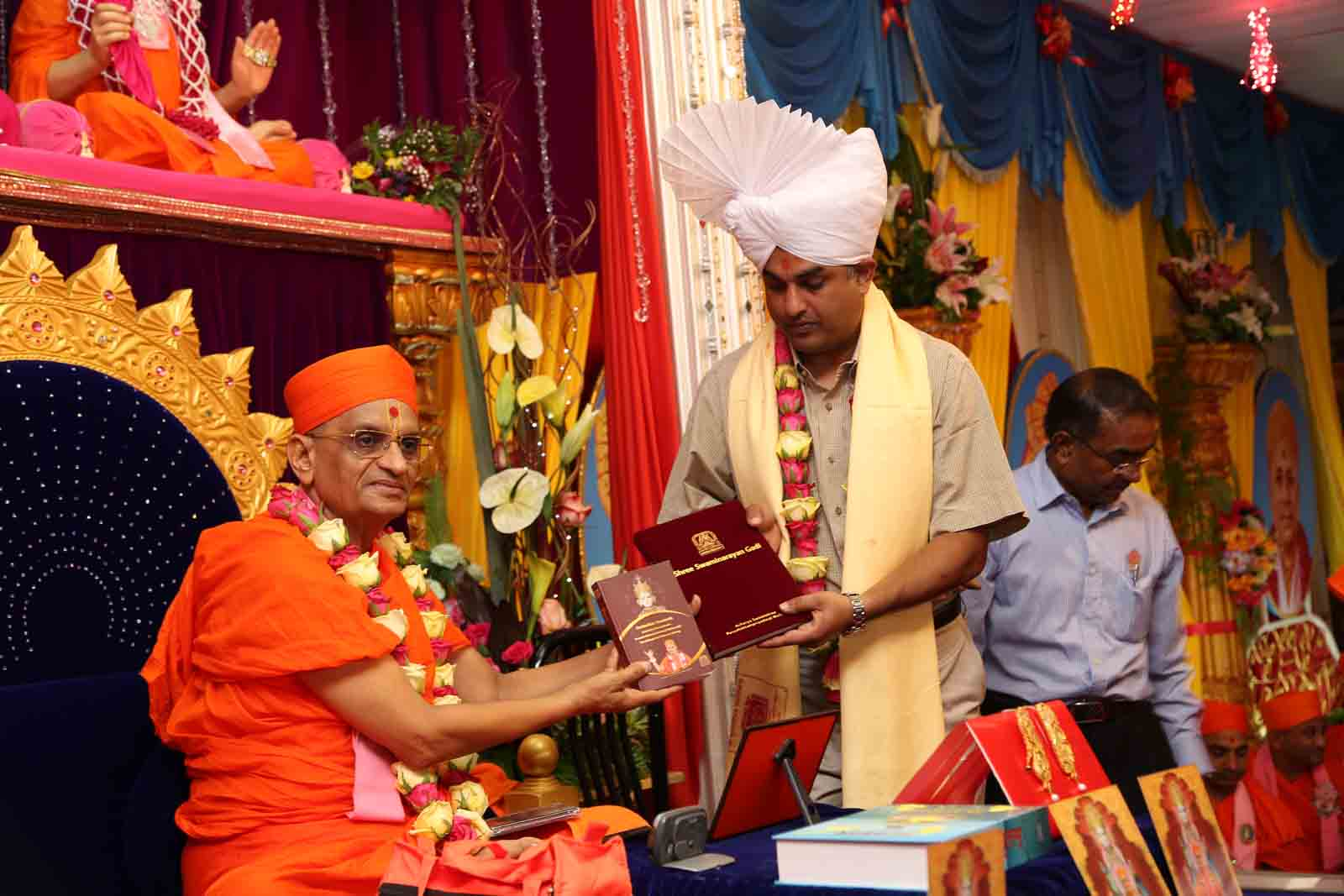 The guest receives 'Shree Swaminarayan Gadi' and 'Sadachar Sandesh'from Acharya Swamishree