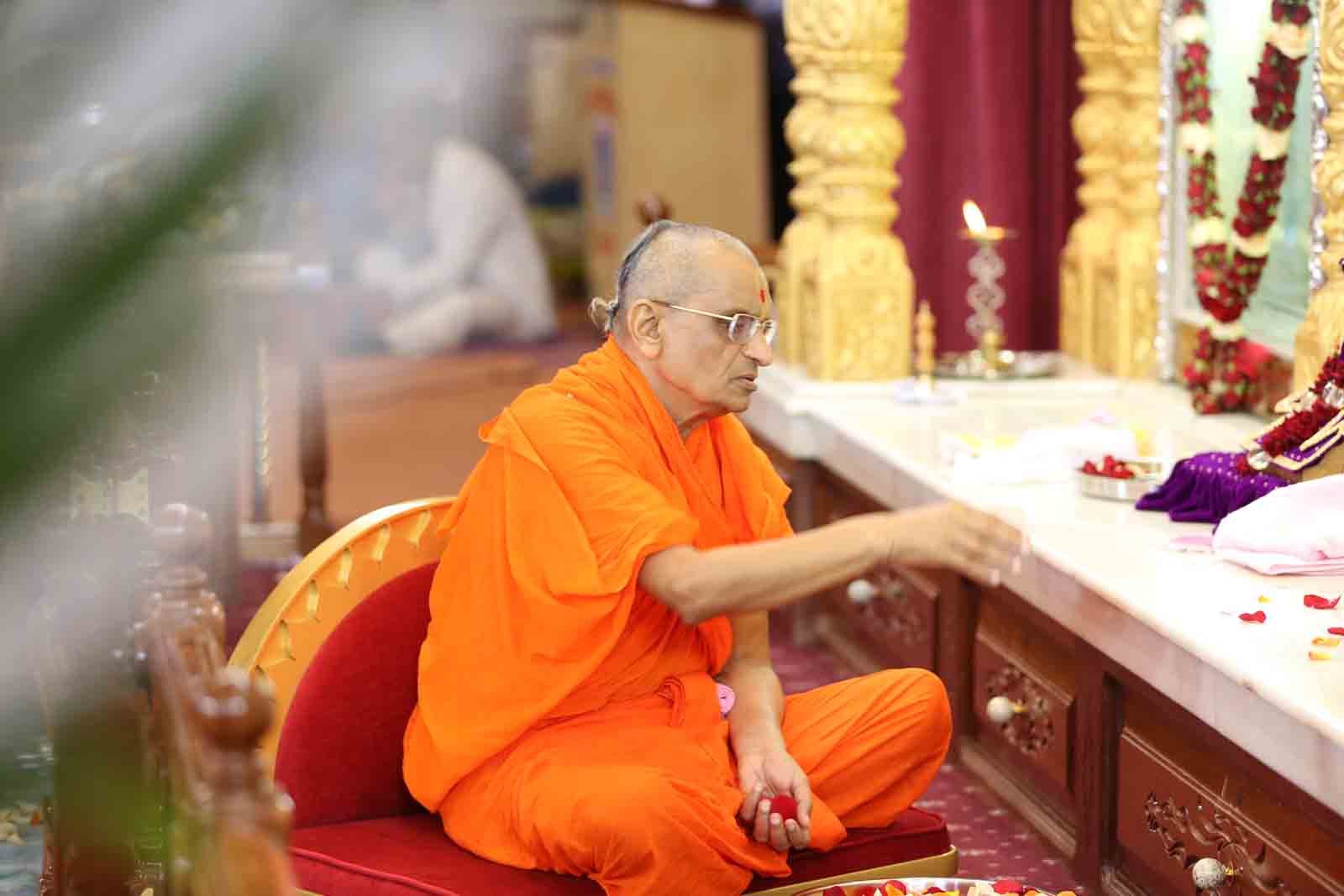 Acharya Swamishree chants sacred verses as He places flowers at the lotus feet of the Lord