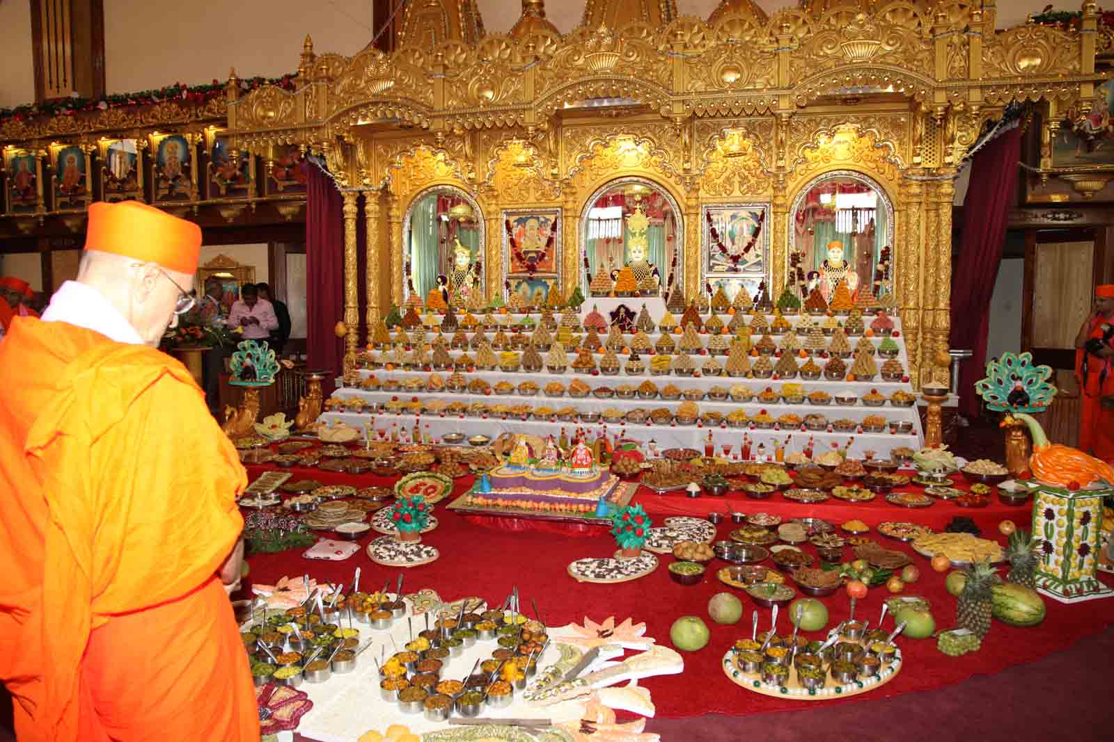 Acharya Swamishree admires the annkut thaar prepared by the sants and devotees