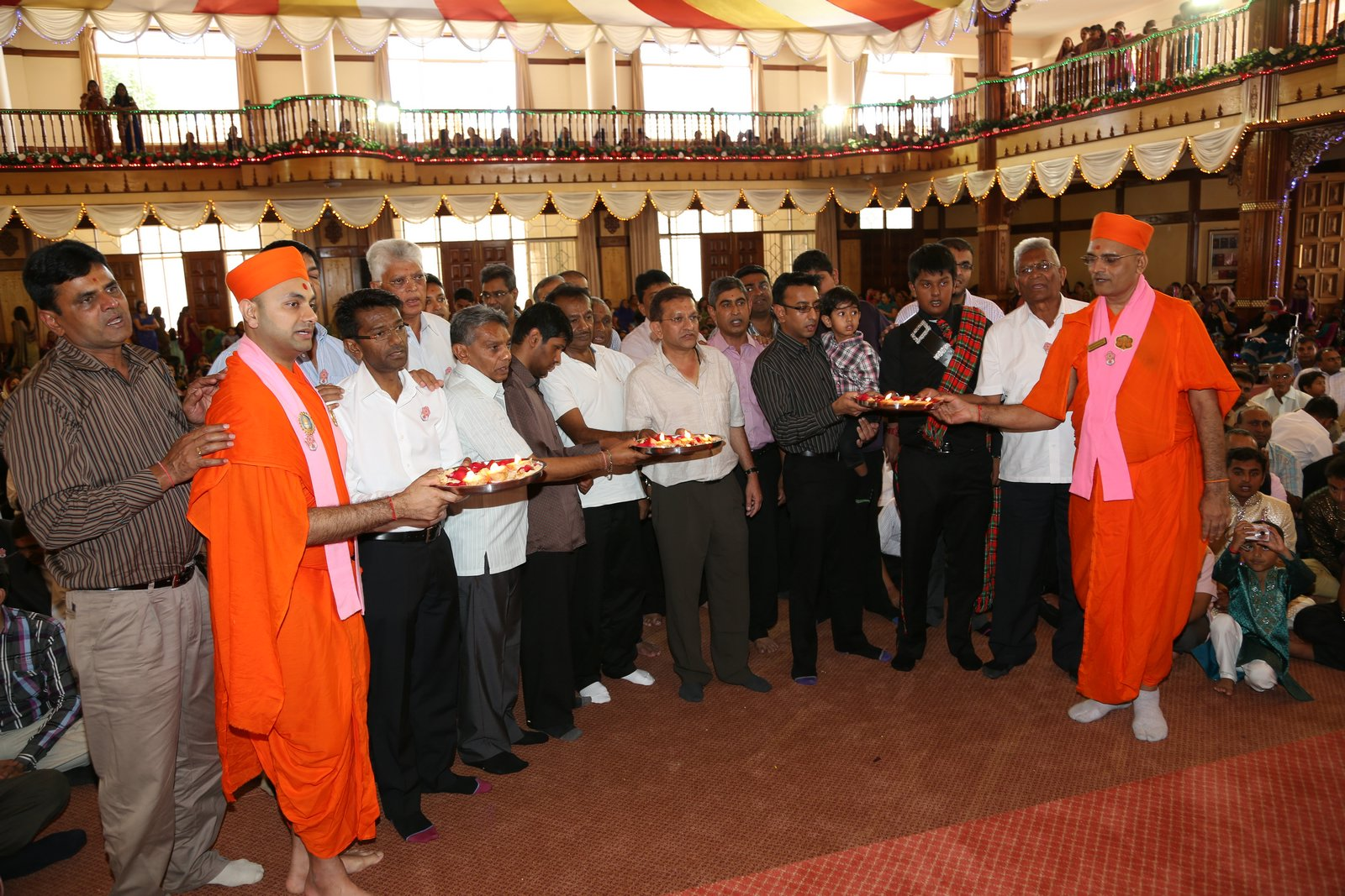 Devotees perform tula aarti to Lord Swaminarayan and Acharya Swamishree