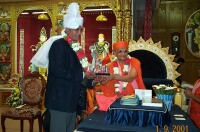 Lord Dholakia receiving a momento from HDH Acharya Swamishree