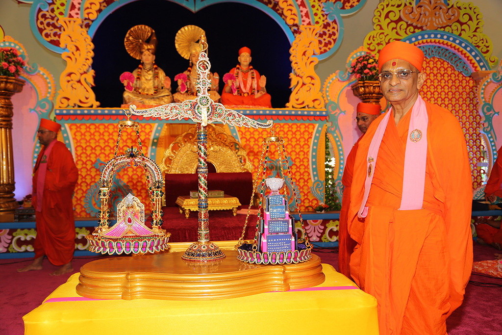 The beautiful murti of Shree Harikrushna Maharaj was seated upon a miniature throne on one side of the scale. Acharya Swamishree and sants then placed sugar crystals (saakar) on the other side of the scale. The tick mark on the scale slowly began to change position as the weight of the sugar crystals increased to one kilogram. Finally, when the weight of the sugar crystals surpassed the physical weight of Shree Harikrushna Maharaj's murti, the side of the scale with His idol ascended higher than the other, and there were cries of joy all around. Acharya Swamishree and sants spun the scale around for the entire audience to have the divine darshan of Harikrushna Maharaj's idol during the Tula. In a similar manner, Shree Harikrushna Maharaj was then weighed against one kilogram of silver, gold, and platinum in the form of bars and coins. Each time the scale tipped from one side to the other, there were ecstatic cries of joy from all over.