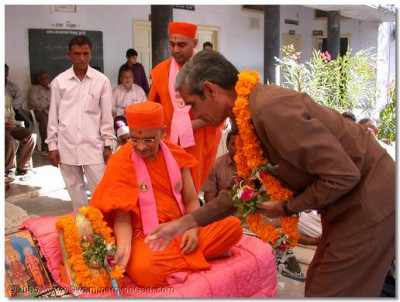 The headmaster of the schol presents HDH Acharya Swamishree with a flower