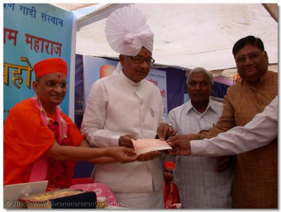 HDH Acharya Swamishree and Professor Mangalbhai Patel donating a cheque