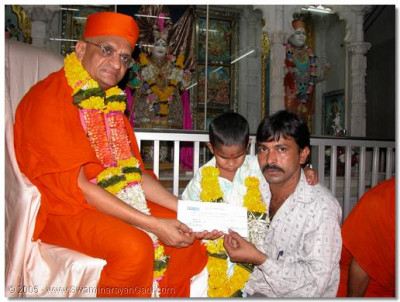 Acharya Swamishree presents a cheque for Mahesh's further treatment