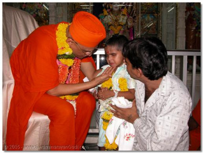 Mahesh is blessed by Acharya Swamishree's caring, divine touch