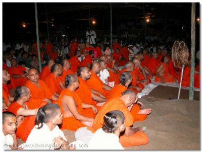 Acharya Swamishree, sants, and devotees watch the dances and the drama.