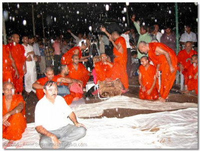 Acharya Swamishree continues to watch the drama during the rain fall