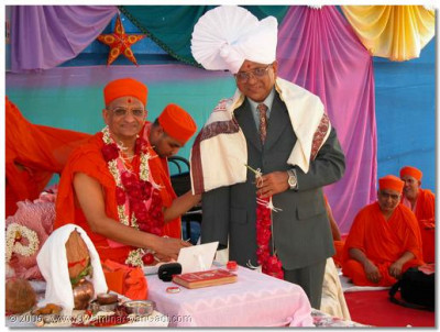 Acharya Swamishree presents Shree K A Pooj with a prasad paag