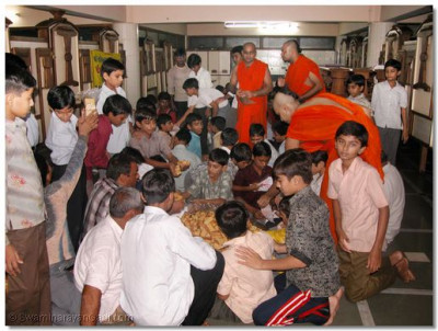 Sants and disciples prepare packages for distribution at Maninagar Temple, Ahmedabad