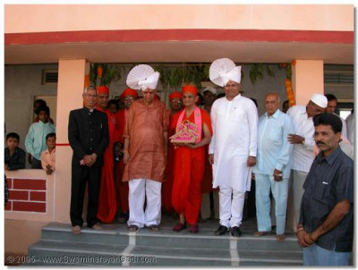 Acharya Swamishree gives darshan with the two eminent dignitaries at the foyer of the school