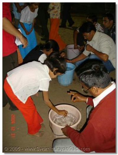 Money Pot event where a coin has to be drop in a bucket of water. The coin must land in a cup at the bottom of the bucket.