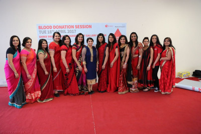 Disciples dressed largely in red who donated blood at Shree Swaminarayan Mandir Bolton
