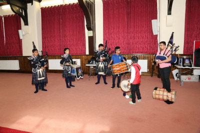 Young disciples perform dhol with members of Shree Muktajeevan Swamibapa Pipe Band bolton