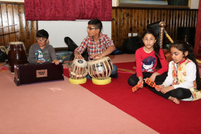 Young disciples perform on the Harmonium and play tabla