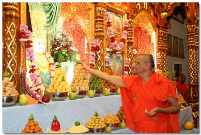 Acharya Swamishree offers prasad cake to Lord Swaminarayan