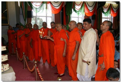 Acharya Swamishree and sants perform aarti to Lord Swaminarayan.