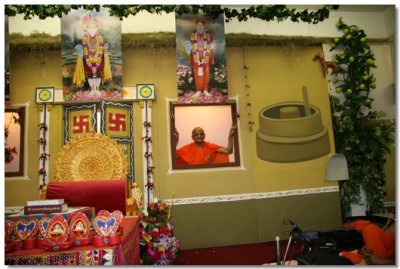 HDH Acharya Swamishree looks upon his devotees through a window of a traditional village house.