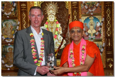 A dignitary receives a momento from Acharya Swamishree.