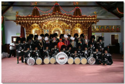 Shree Swaminarayan Gadi Pipe Band group photo showing off their new feather bonnets.