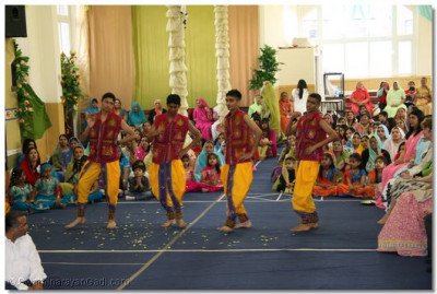 Teenage boys doing a dance in traditional costumes.