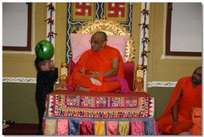 Youing boy showing ball dance to please Acharya Swamishree.