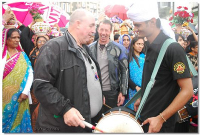 An onlooker attempts to play the dhol