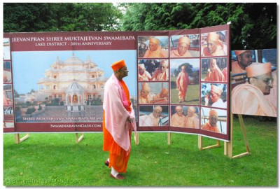 Acharya Swamishree closely looks at all the images on display