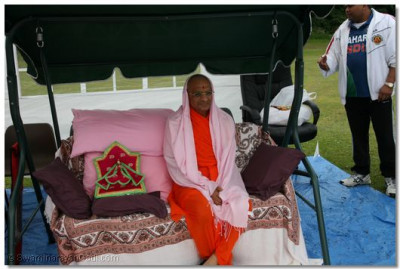 Divine darshan of Acharya Swamishree and Shree Harikrishna Maharaj seated on a swing
