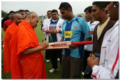 Acharya Swamishree autographs a cricket bat for a disciple