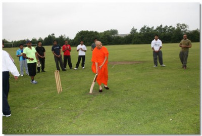 Acharya Swamishree holding a cricket bat awaiting a delivery