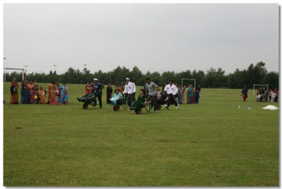 Disciples take part in the wheel barrow race with real wheel barrows