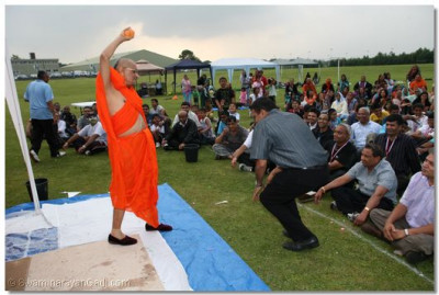 Acharya Swamishree prepares to throw a filled water balloon