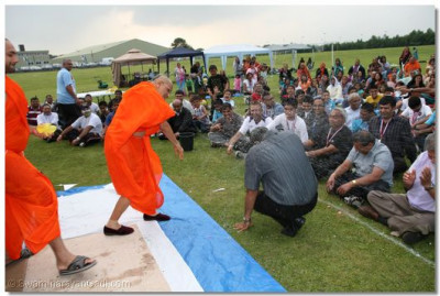 Acharya Swamishree blesses a disciple with a filled water balloon
