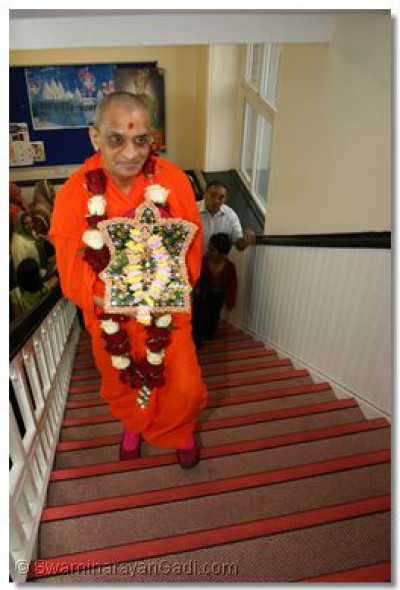 His Divine Holiness Acharya Swamishree wlaks up the stairs to the sabha hall.