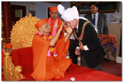Acharya Swamishree blesses the Mayor with a chandlo