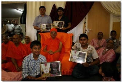 His Divine Holiness Acharya Swamishree presents a number of educational excellance awards to disciples