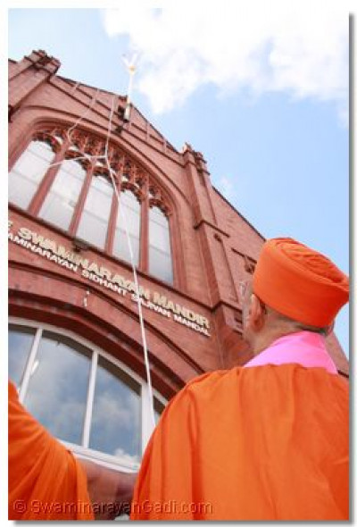 His Divine Holiness Acharya Swamishree hoists the new temple flag to the top of Shree Swaminarayan Temple Bolton