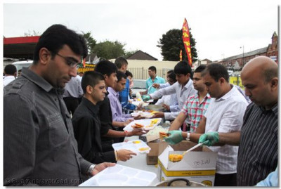 Disciples serve and eat delicious prasad lunch