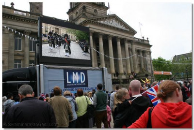 Shree Swaminarayan Gadi Pipe Band shown on large screen to the crowds at at Victoria Square, Bolton