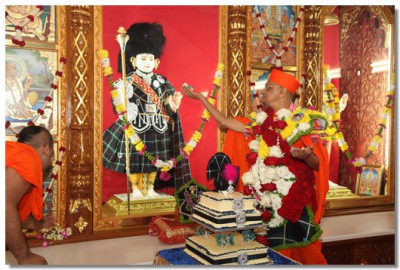 His Divine Holiness Acharya Swamishree offers cake to Lord Swaminarayan