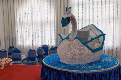 The cake stand is a magnificent rotating swan crafted entirely from folded card and paper