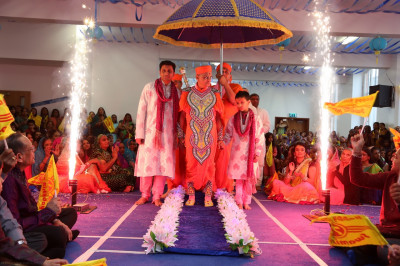 Disciples and Sants escort His Divine Holiness Acharya Swamishree onto the stage as fireworks light up the hall