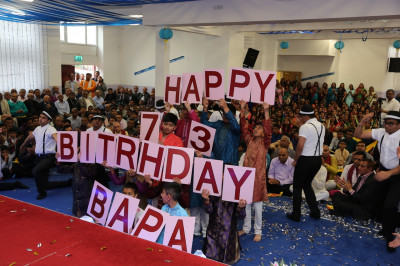 Young disciples hold cards spelling out the 'Happy Birthday' message
