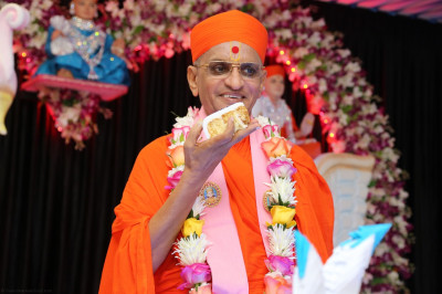 His Divine Holiness Acharya Swamishree holds the delicious piece of prasad cake
